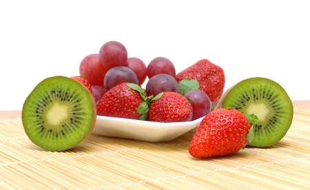 ripe juicy berries and fruits. kiwi, strawberries and grapes on a white background