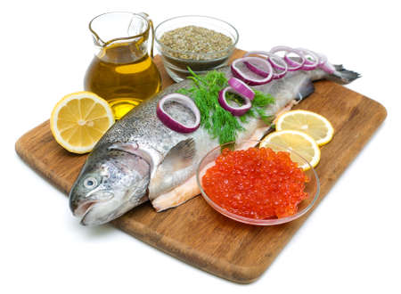 trout, vegetables, red caviar, olive oil, lemon and spices isolated on white background photo