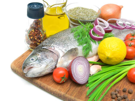 fresh trout, vegetables, lemon, olive oil and spices on a cutting board on a white background close-up Stock Photo - 17534616