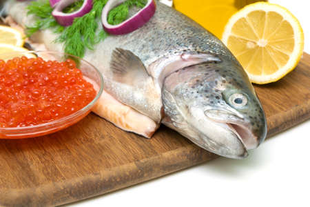 trout with vegetables, red caviar in a glass bowl and lemon close up on wooden cutting board photo