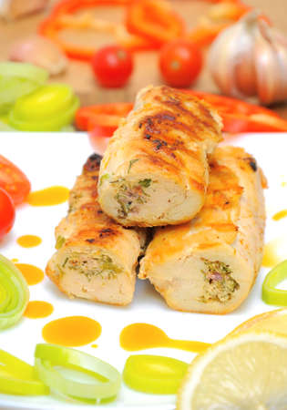 Chicken rolls stuffed with feta cheese, fresh herbs, sun-dried tomatoes with vegetables closeup Stock Photo