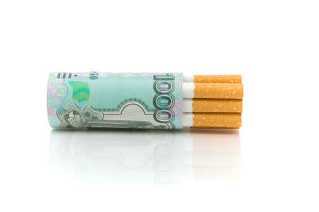 banknote and a cigarette on a white background with reflection closeup  harmful expensive habit  photo