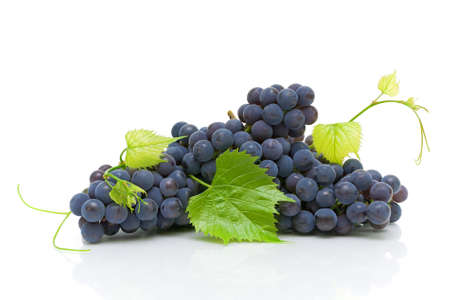 Bunch of ripe dark grape with green leaves close up on white background