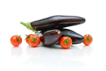 ripe cherry tomatoes and three eggplant on a white background close-up. horizontal photo. Stock Photo - 18513159