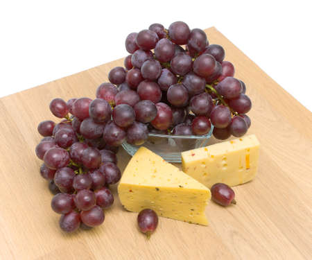 bunch of ripe grapes and cheese on a cutting board on a white background. Top view. Stock Photo - 18786426