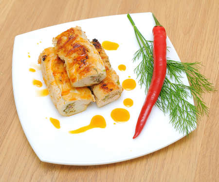 Chicken rolls, chili and dill on a plate close-up. Horizontal  photo  - top view. Stock Photo - 18786428