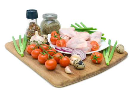fresh vegetables, spices, quail eggs and raw chicken wings on chopping board isolated on white background photo