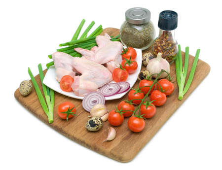 raw chicken wings, vegetables, eggs and spices on a white background. horizontal photo. photo