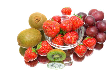 kiwi, strawberries and dark grapes on a white background with reflection. top view photo