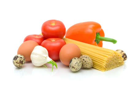 garlic, quail and chicken eggs, ripe tomatoes, pasta and sweet peppers on a white background. Stock Photo