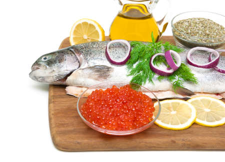 Red caviar in a glass bowl and fresh trout on a cutting board on a white background. horizontal photo. photo