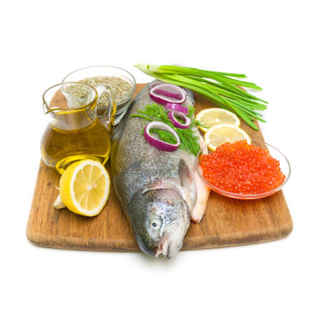 fresh raw trout, vegetables, olive oil, lemon, spices and red caviar on white background. vertical photo. photo