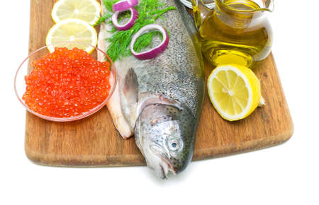 fresh fish trout, red caviar in a glass bowl, vegetables, lemon and spices on a cutting board on a white background. view from above. horizontal photo. photo