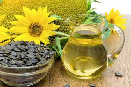 sunflower oil in a glass decanter, sunflowers and ripe seeds close-up  horizontal photo  photo