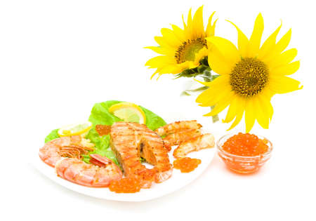 grilled fish with lemon, red caviar and shrimp on a plate and sunflowers isolated on white background. horizontal photo. photo