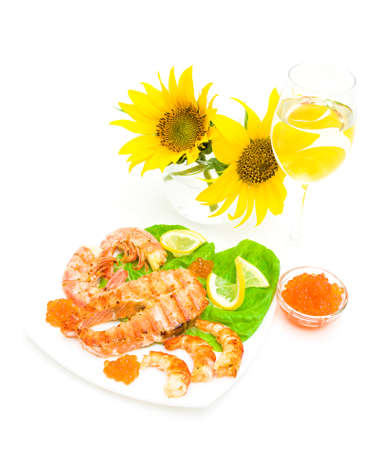 grilled fish with lemon, red caviar and shrimp, a glass of wine and sunflowers isolated on white background. vertical photo. photo