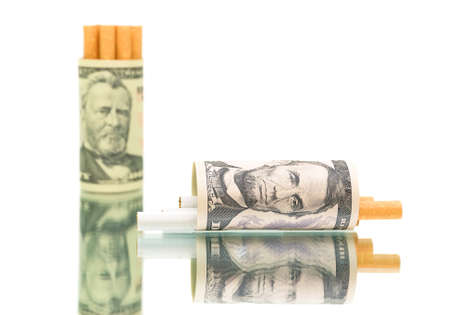 expensive habit. money (U.S. dollars) and a cigarette on a white background with reflection close-up. horizontal photo. photo