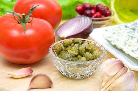 Pickled capers in a glass bowl close-up, vegetables, cheese and cranberries on a cutting board. horizontal photo. photo