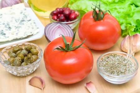 fresh food. tomatoes, garlic, onions, capers, cheese and cranberries close-up - horizontal photo. photo