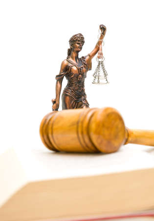 Statue of justice on a white background. Gavel and law book in the foreground out of focus. vertical photo. photo