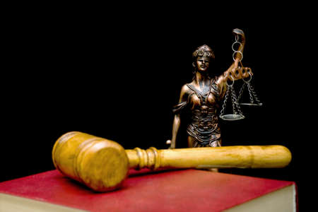 judicature: Statue of justice on a black background. Gavel and law book in the foreground out of focus. Horizontal photo.
