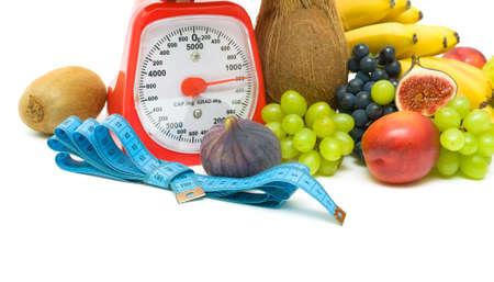 measuring tape, kitchen scales and fresh fruit on a white background. horizontal photo. Stock Photo