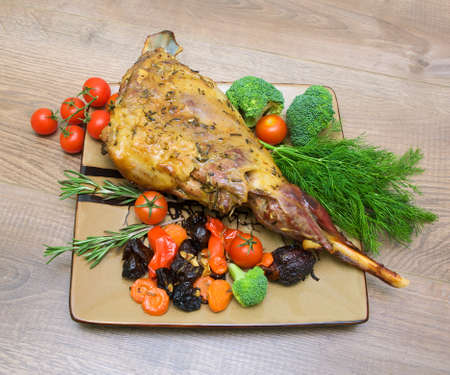 roasted leg of lamb with vegetables, greens and prunes on a plate on a wooden table. photo