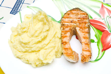 succulent grilled salmon and mashed potatoes on the plate. horizontal photo. photo