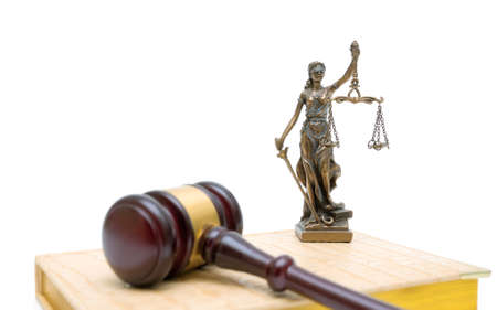 statue of justice, gavel and book on a white background. horizontal photo.