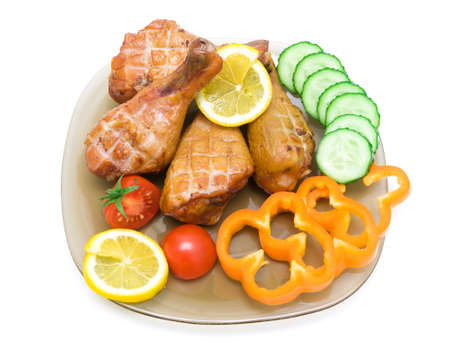 smoked chicken legs with vegetables and lemon on a plate on a white  photo