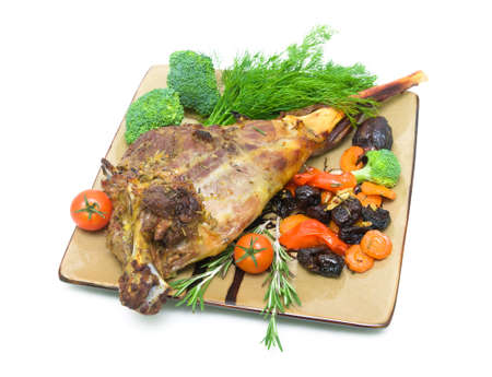 roasted leg of lamb with vegetables, prunes and herbs on a plate isolated on a white