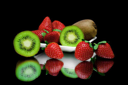 fresh juicy kiwi and strawberries on a plate on a black background with mirror reflection. horizontal photo. photo