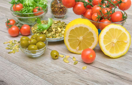 lemon, olives and other fresh food on a wooden table closeup. horizontal photo. photo
