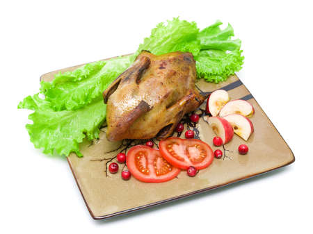 roast wild duck carcass with lettuce, tomatoes, apples and cranberries on a plate on white background   photo