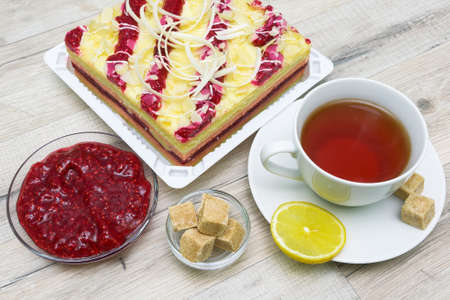 cup with tea, cake and raspberry jam on a wooden table.  photo