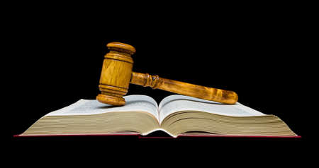 adjourned: Gavel lies on the open book isolated on a black background.