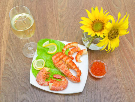 grilled fish with lemon, red caviar and shrimp, a glass of wine and sunflowers on a wooden background. horizontal photo. photo