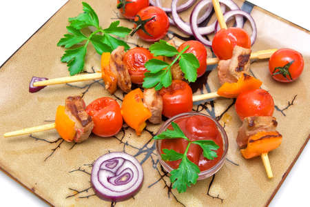 skewers of meat with vegetables on a plate on a white background. horizontal photo. photo