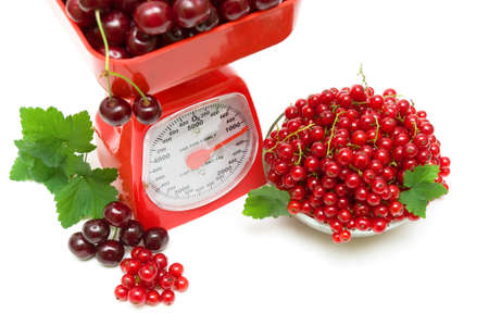 ripe juicy red currant berries and cherries and kitchen scales on a white background. horizontal photo. photo