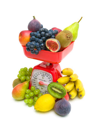fresh fruit and kitchen scales close up on a white background. vertical photo. photo