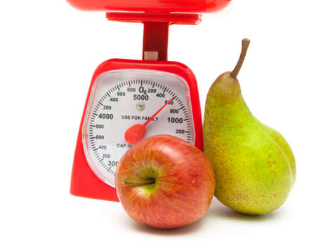 ripe red apple, pear and kitchen scales close up on a white background. horizontal photo. photo