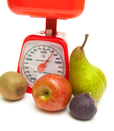ripe fruit and kitchen scales close up on a white background. vertical photo. photo