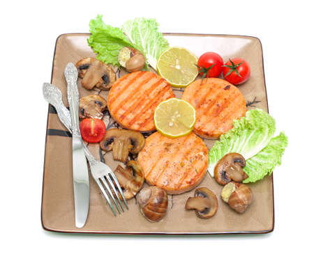 fried medallions of salmon, stuffed snails with mushrooms and vegetables on a plate. Isolated on white background. photo