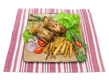 dish with fried woodcock and vegetables on a napkin isolated on white background. horizontal photo.