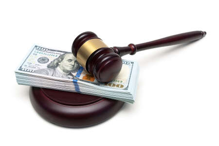 gavel and a big wad of money isolated on white background. horizontal photo.