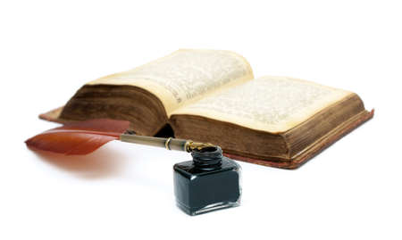 inkwell, pen and an old open book isolated on white background close-up. horizontal photo.