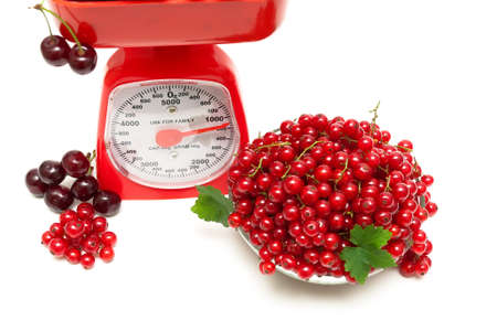 red gram: red currants and kitchen scales on a white background. horizontal photo. Stock Photo