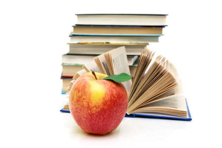 erudition: ripe apple and books on a white background. horizontal photo.