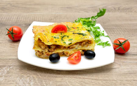Lasagna with minced meat on a white plate on a wooden background. horizontal photo. Stock Photo