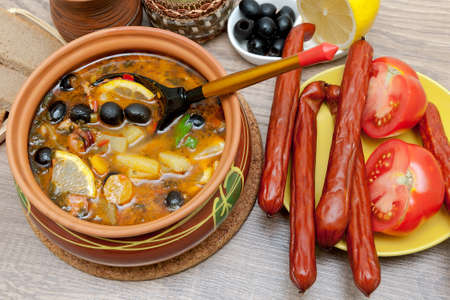 appetizing dish of russian hodgepodge soup in ceramic pot. horizontal photo.